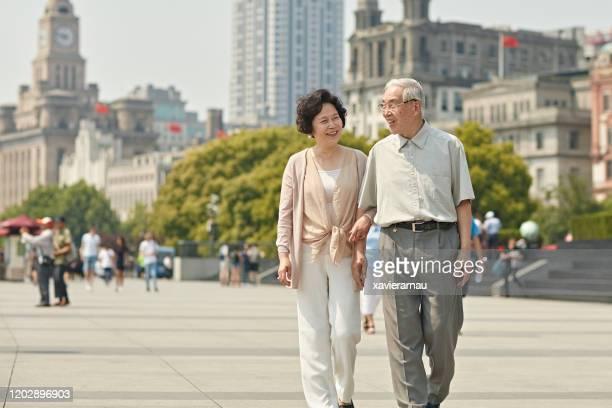 smiling senior chinese couple enjoying walk along the bund - approaching stock pictures, royalty-free photos & images