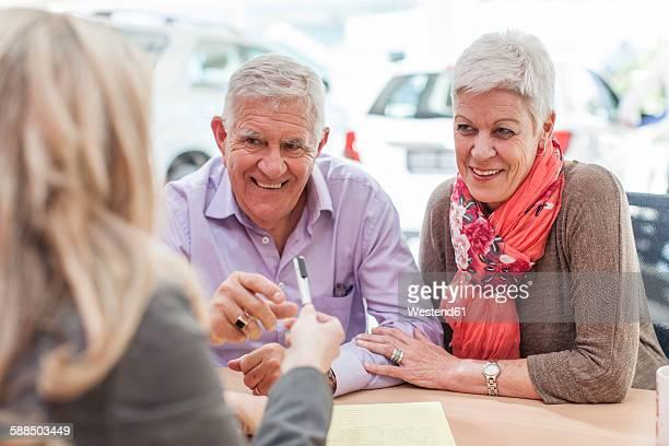 Smiling senior couple at car dealer