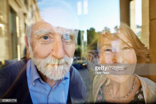 Smiling senior couple behind window pane