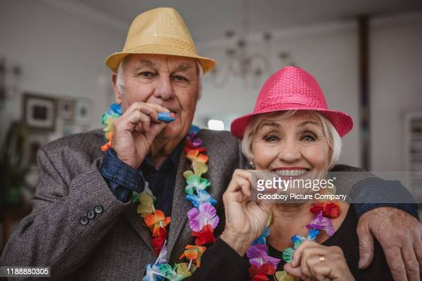 smiling senior couple blowing party horns on new year's eve - 70 year old man stock pictures, royalty-free photos & images