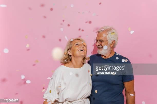 le couple aîné de sourire célèbre leur anniversaire - anniversaire d'un évènement photos et images de collection