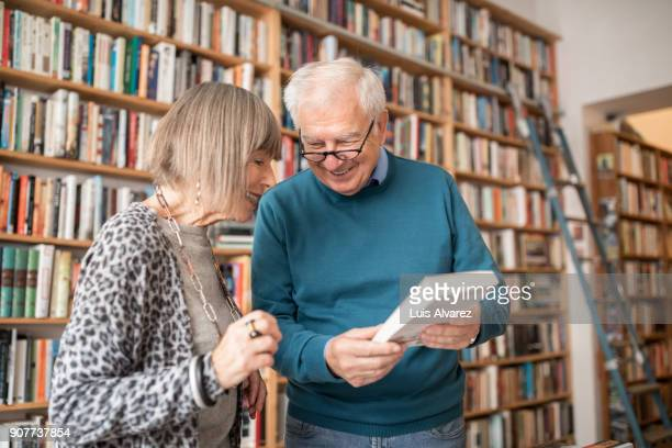 Smiling senior couple choosing book
