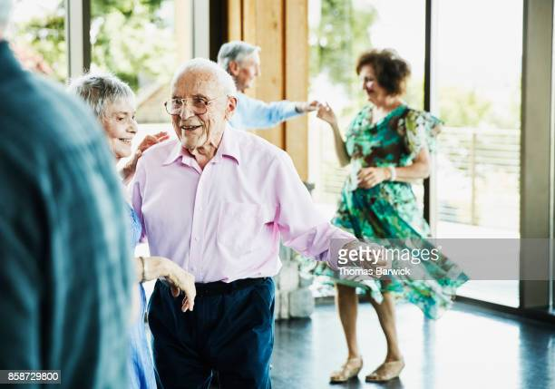 smiling senior couple dancing together during dance in community center - image stock pictures, royalty-free photos & images