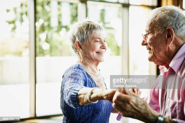 Smiling senior couple dancing together in community center