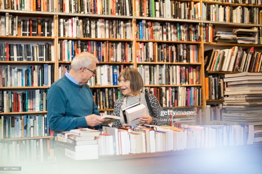 Smiling senior couple discussing while choosing book : Stock Photo