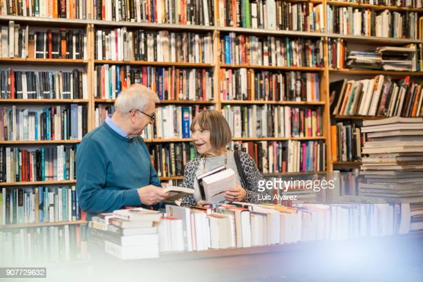 smiling senior couple discussing while choosing book - book shop stock pictures, royalty-free photos & images