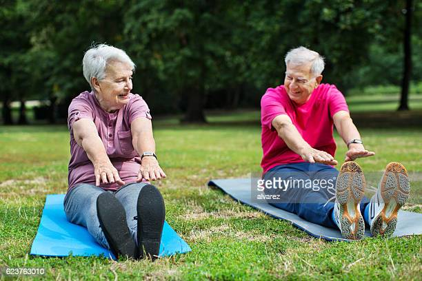 Smiling senior couple doing exercise in park