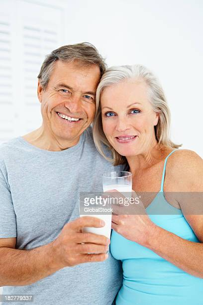 Smiling senior couple drinking a glass of milk together