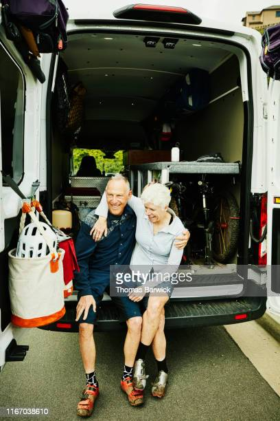 smiling senior couple embracing while sitting on back of camper van after mountain bike ride - heterosexual couple stock pictures, royalty-free photos & images