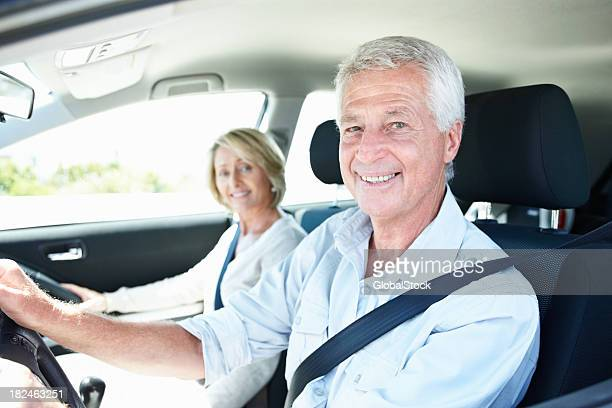 Smiling senior couple enjoying a car ride