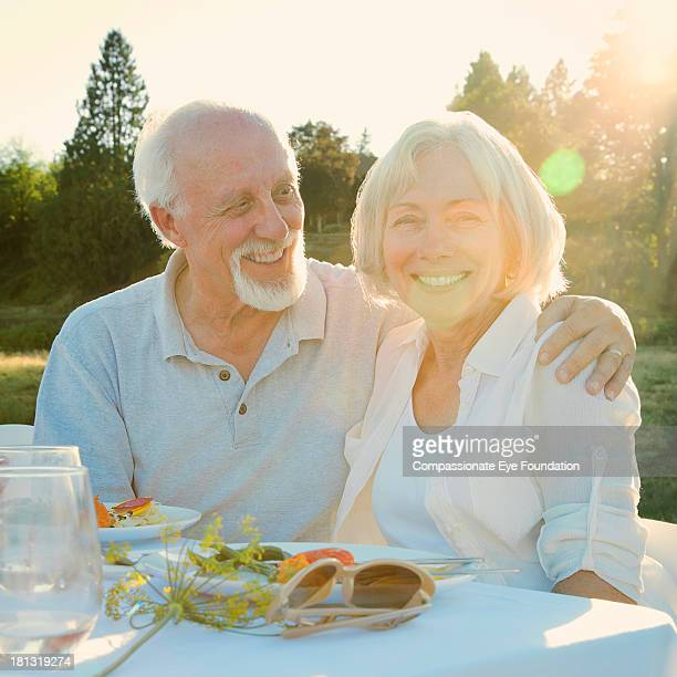 Smiling senior couple having lunch outdoors