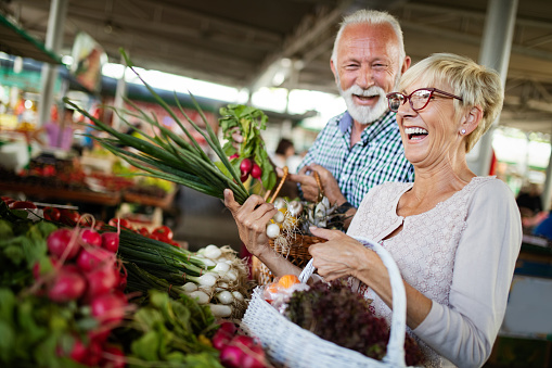 Smiling senior couple holding basket with vegetables at the market 1051724302