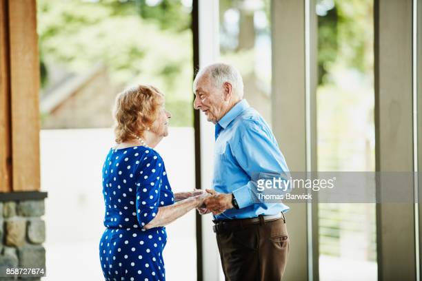 Smiling senior couple holding hands after dancing in community center