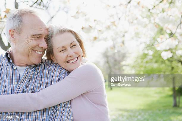 smiling senior couple hugging in park - senior couple stock photos and pictures