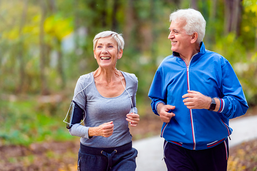 Smiling senior couple jogging in the park 1060929022