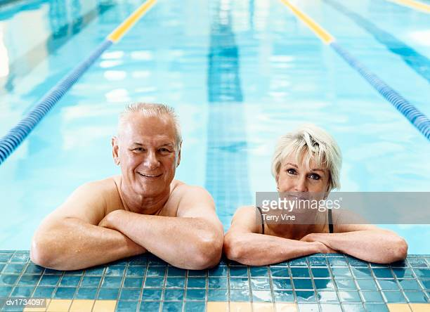 smiling senior couple leaning on the side of a swimming pool - alte frau badeanzug stock-fotos und bilder