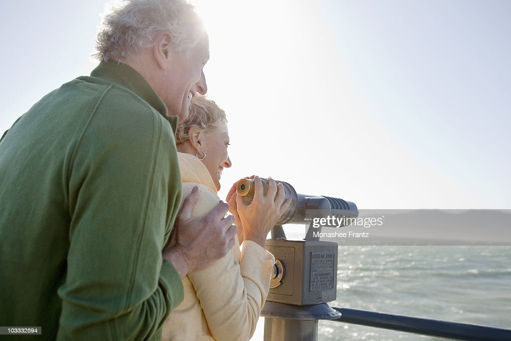 Smiling senior couple looking at ocean with coin-operated binoculars : Stock Photo