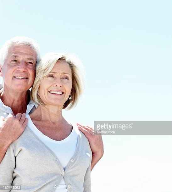 Smiling senior couple looking away while outdoors