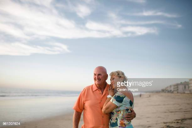 smiling senior couple looking away while standing at beach against sky during sunset - carlsbad california stock pictures, royalty-free photos & images