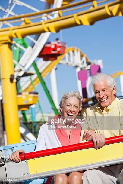 Smiling senior couple on amusement park ride
