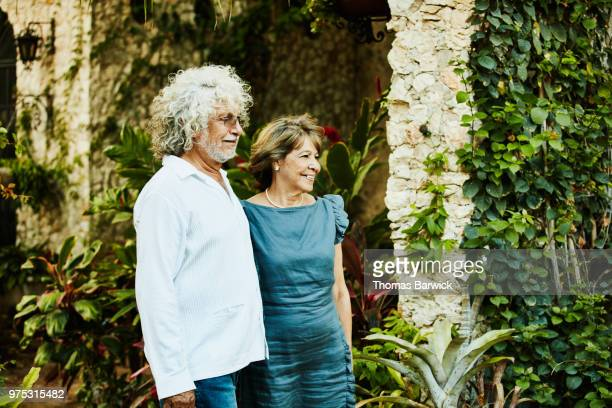 Smiling senior couple posing for photo in backyard garden during family dinner party
