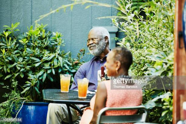 smiling senior couple sharing drinks at outdoor cafe on summer afternoon - real wife sharing stock photos and pictures