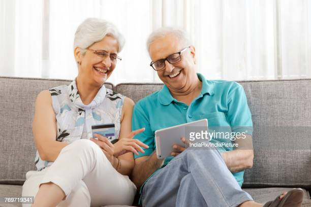 Smiling senior couple shopping online using credit card on digital tablet