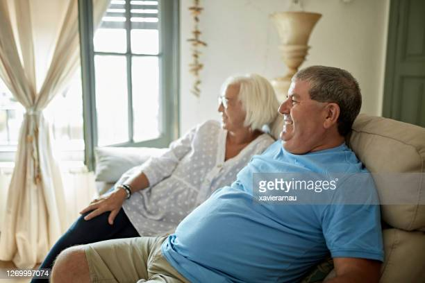 smiling senior couple sitting on sofa and watching tv - two seater sofa stock pictures, royalty-free photos & images