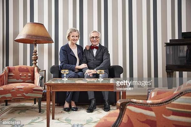 Smiling senior couple sitting on sofa with champagne glasses