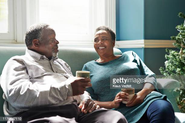 smiling senior couple talking on sofa at home - wife stock pictures, royalty-free photos & images