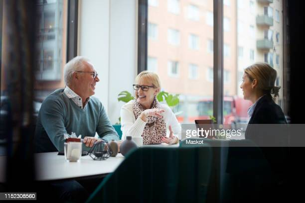 smiling senior couple talking while sitting with realtor in office - financial planning stock pictures, royalty-free photos & images