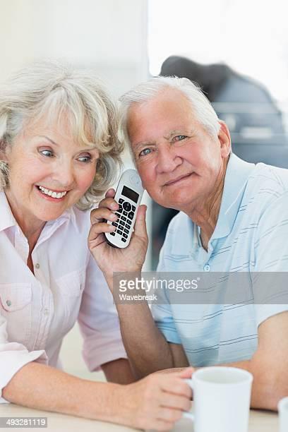 Lächelnd altes Paar mit cellphone zusammen