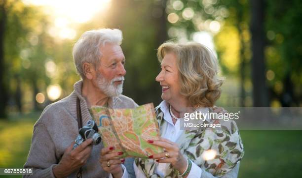Smiling senior couple using map at the nature