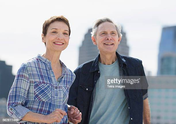 Smiling senior couple walking in city
