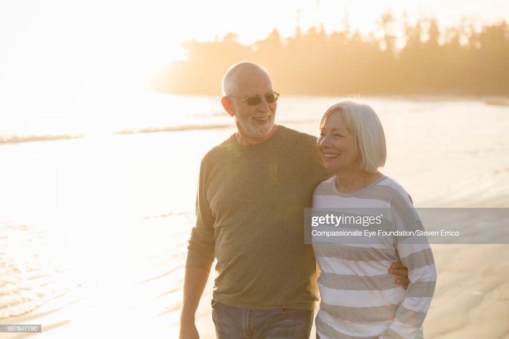 Smiling senior couple walking on beach at sunset : Stock Photo