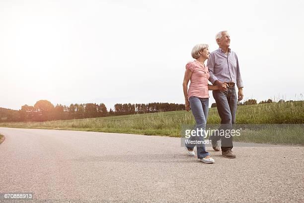 smiling senior couple walking on country road - gehen stock-fotos und bilder