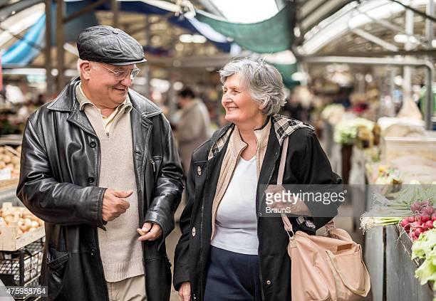 Smiling senior couple walking through farmer's market and talking.