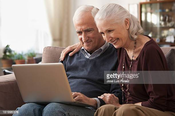 smiling senior couple with laptop - marryornot stock pictures, royalty-free photos & images