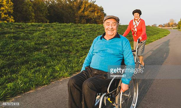 Smiling senior couple with wheelchair and wheeled walker on a path