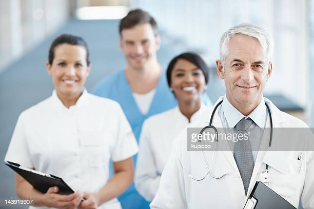 Smiling senior doctor with medical team in the background
