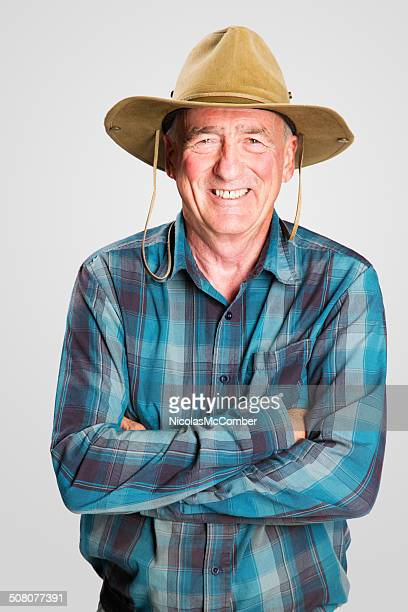 Smiling senior farmer arms crossed studio hat plaid shirt