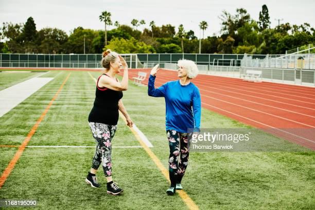 Smiling senior female athletes high fiving after workout on track