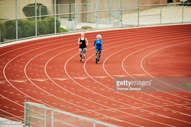 Smiling senior female friends racewalking on track