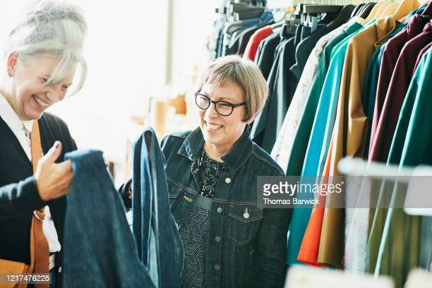 smiling senior female shop owner helping client pick out outfit in boutique - disruptagingcollection stock pictures, royalty-free photos & images