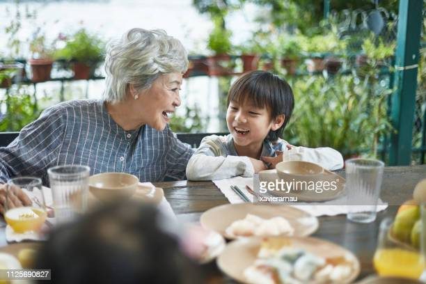 smiling senior having meal with grandson at table - generation gap stock pictures, royalty-free photos & images