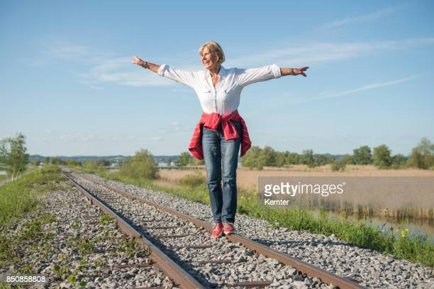 smiling senior lady having fun balancing on rails