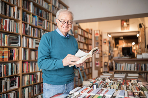 Smiling senior male customer reading book at bookstore - gettyimageskorea