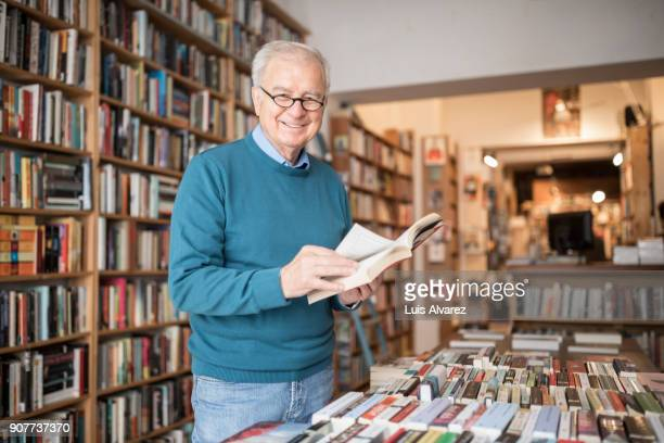 smiling senior male customer reading book at bookstore - man holding book stock pictures, royalty-free photos & images