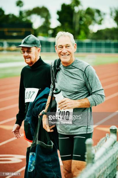 Smiling senior male track athlete walking onto track with friend before meet