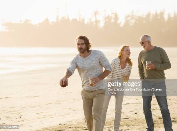 smiling senior man and family playing boules on beach at sunset - mid adult men stock pictures, royalty-free photos & images